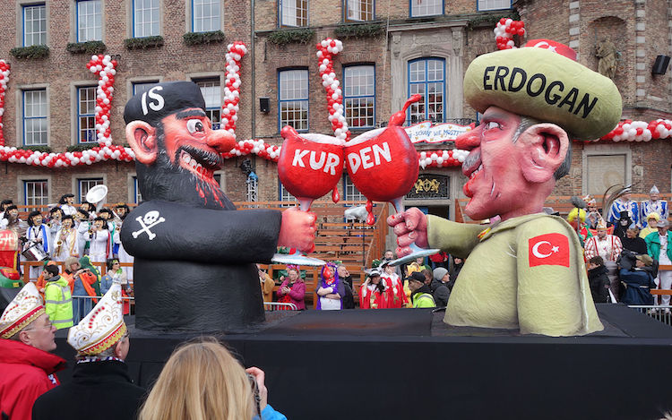 Photo: A carnival float in Duesseldorf depicts Abu Bakr al-Baghdadi and Turkish President Erdoğan, 2016. Abu Bakr is the leader of the Sunni militant jihadist organisation known as the ISIS_Islamic State of Iraq and the Levant, which controls territory in western Iraq, Syria, Libya and Afghanistan. Credit: Wikimedia Commons.