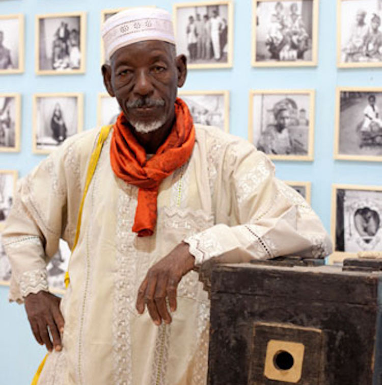 Photo: Oumar Ly poses with his first camera at Fes­ti­val mon­dial des Arts Nègres held in Dakar, Senegal from 10-31 December 2010. Credit: Wikimedia Commons.