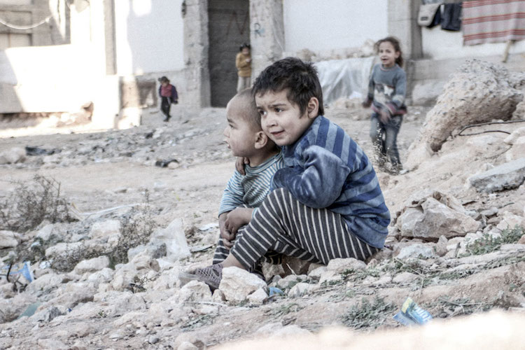 Photo: In Aleppo, Syria, four-year-old Esraa and her brother Waleed, three, sit on the ground near a shelter for internally displaced persons. Credit: UNICEF/UN013175/Al-Issa